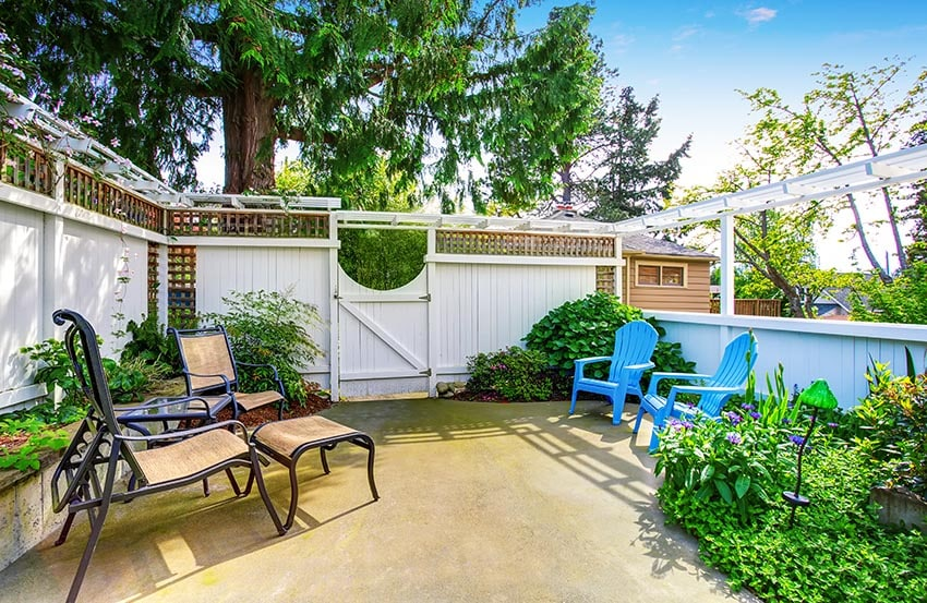 White fence with lattice top and panels in backyard patio with narrow pergola