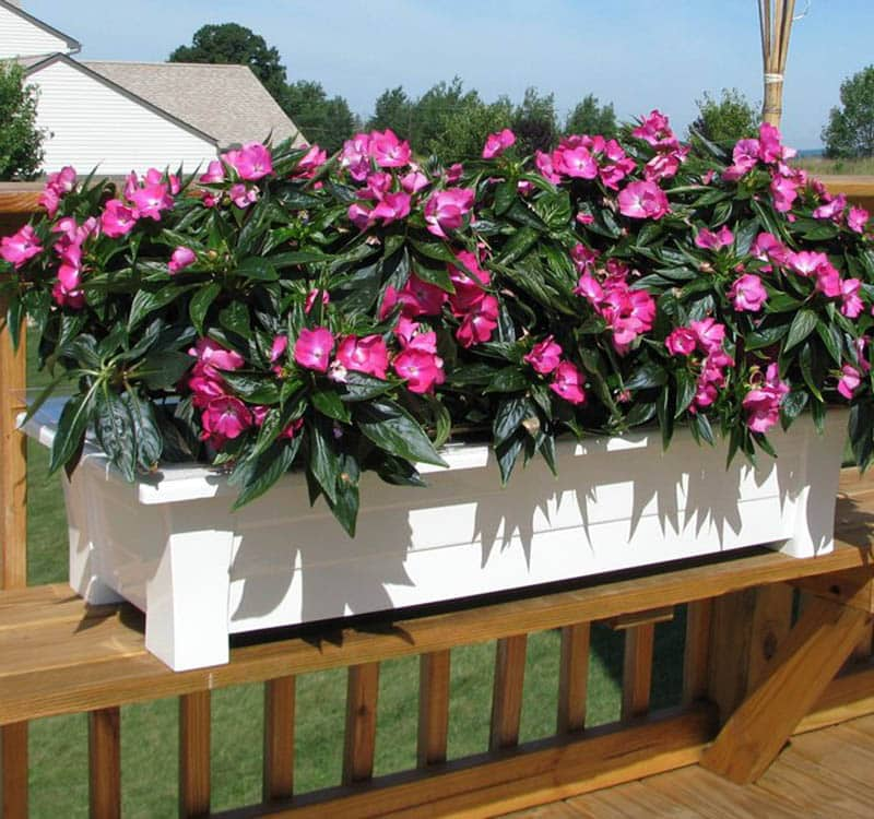 White resin planter box with pink flowers on wood deck