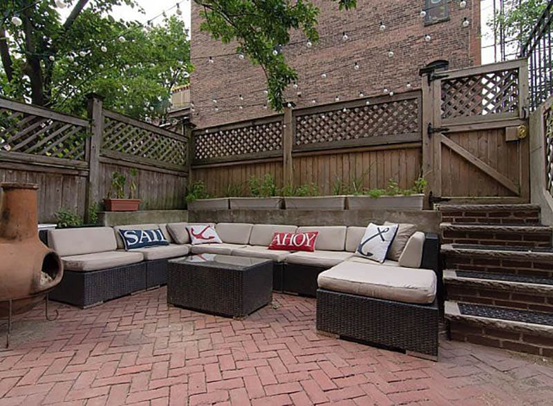 Wood lattice fence surrounding brick patio with outdoor couch
