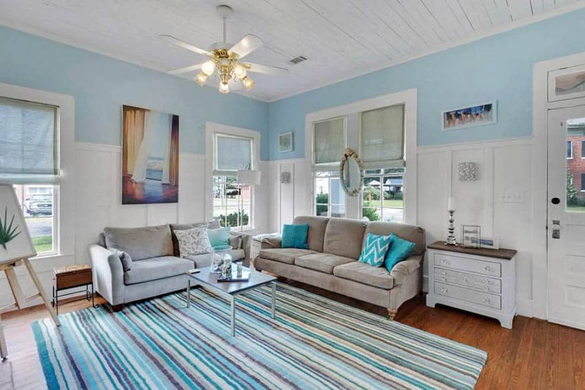Blue and white living room with wainscoting and area rug