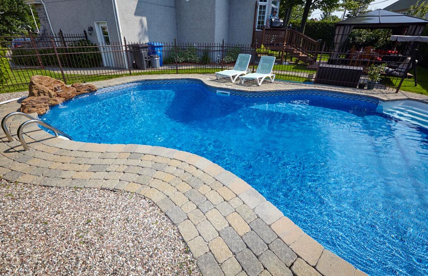 Blue kidney shaped pool with paver border