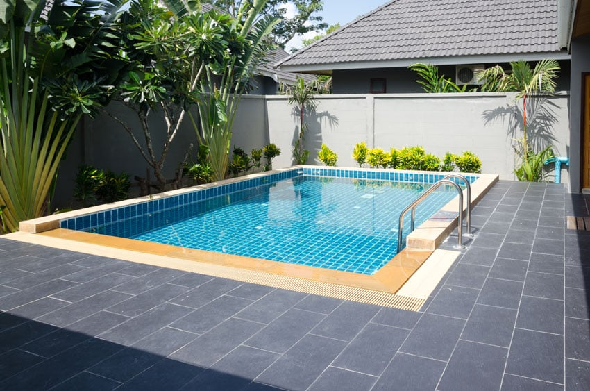 Blue swimming pool with modern patio
