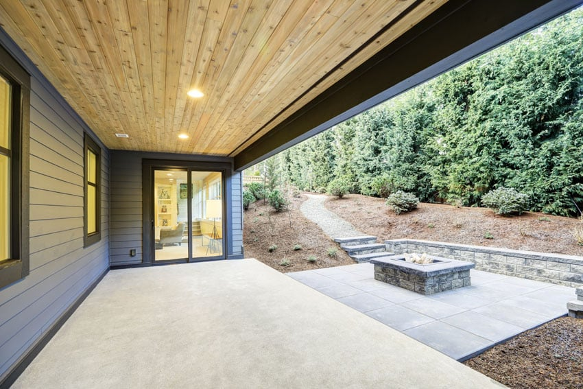 Covered patio in backyard with lower concrete level and stone firepit