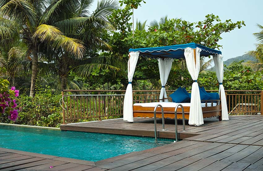 Elevated swimming pool with wood deck and cabana daybed