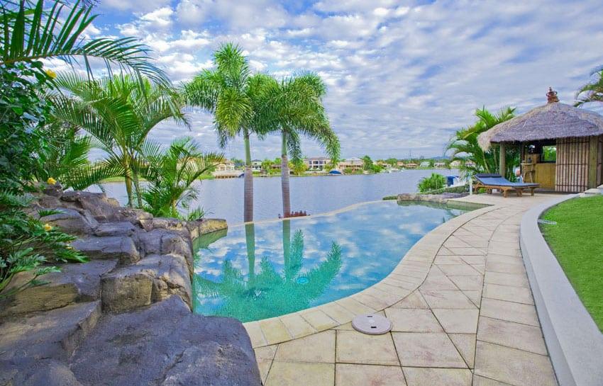 Infinity lagoon pool with river views and tiki hut bar