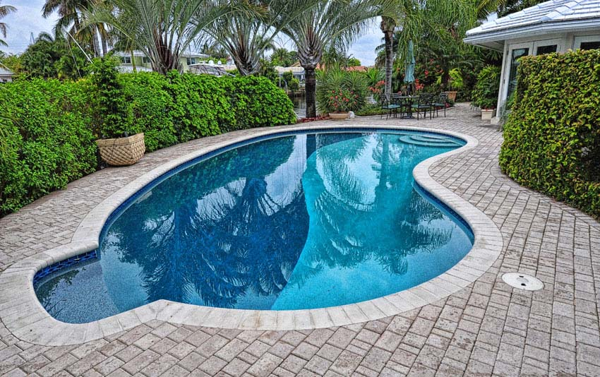Kidney shaped pool with side sitting area and stone patio