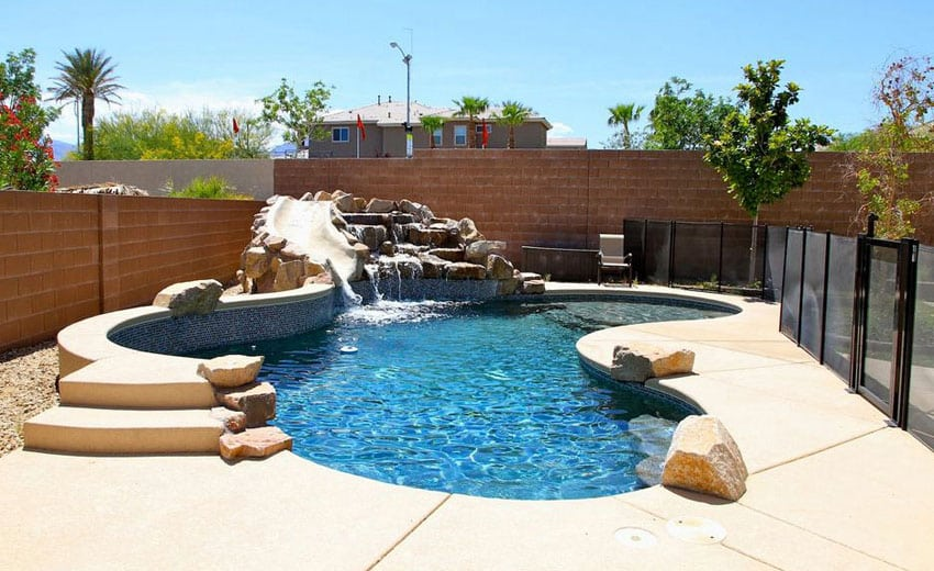 Kidney shaped pool with water feature rock waterfall and slide