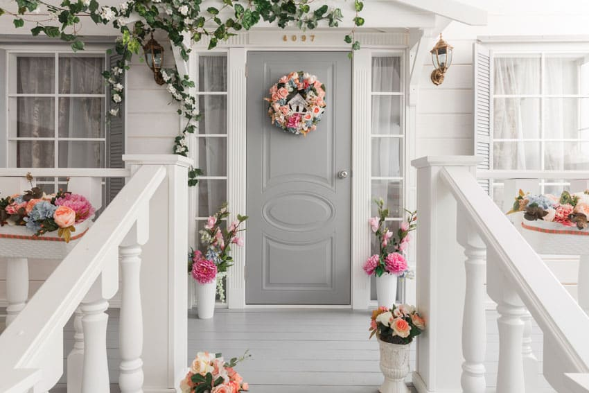 Light gray front door on home with floral decorations