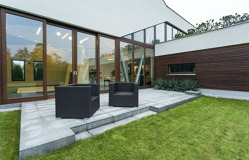 Modern concrete patio with window wall, rattan furniture and grass area