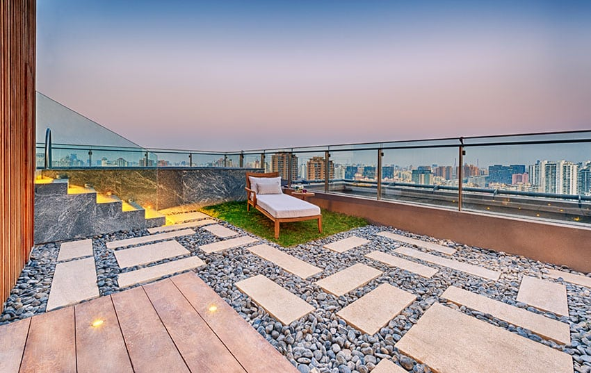 Modern rooftop patio with rocks and grass lounge area