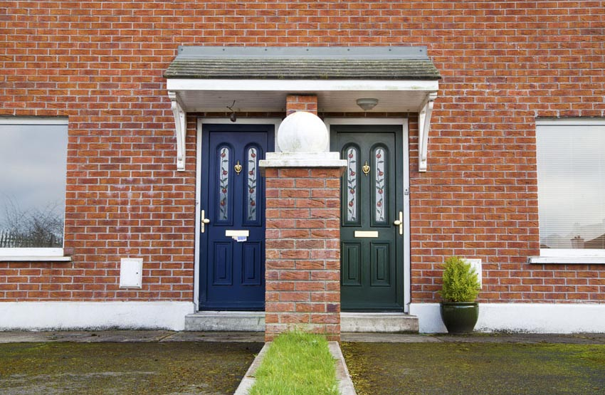 Navy and green front doors on duplex brick house