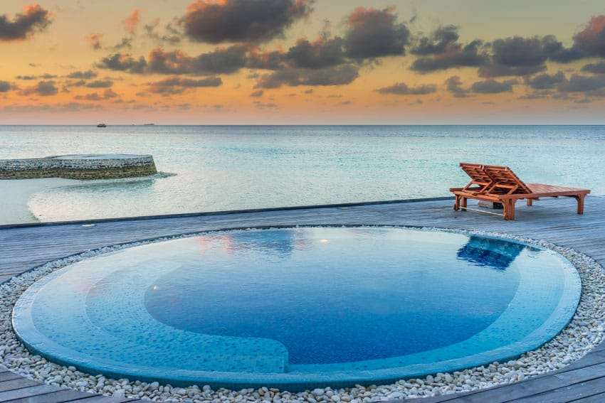 Oceanfront round wading pool with rock border and wood deck