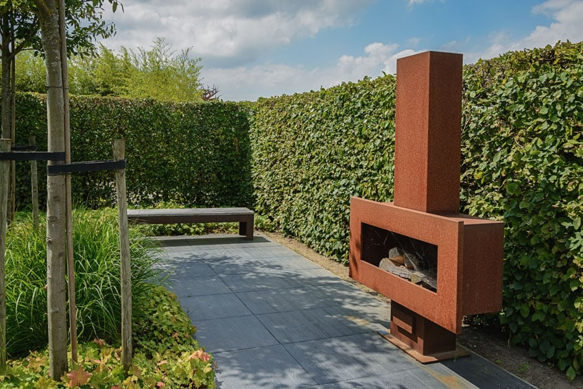 Patio with hedge walls and modern fireplace