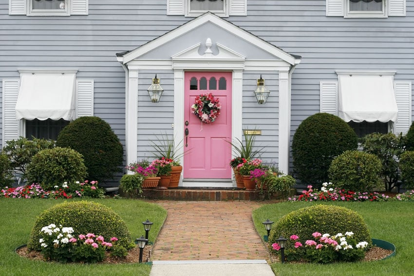 Pink front door on gray house with pink and white flowers