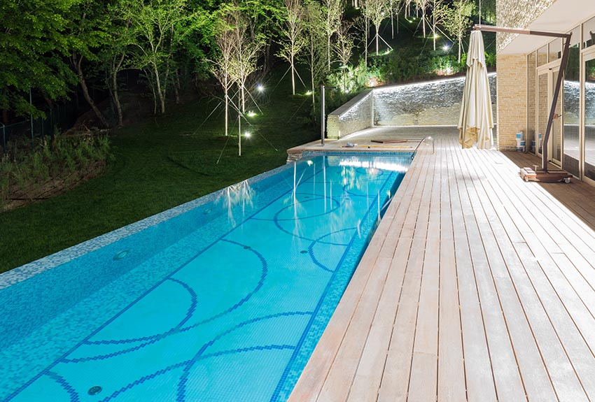 Rectangular swimming pool with curved designs and deck behind modern house