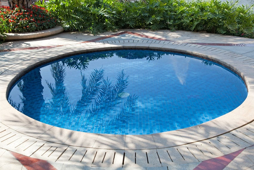 Small round dipping pool with concrete patio
