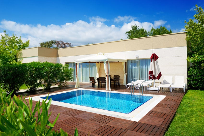 Small inground swimming pool with modern wood deck with canopy