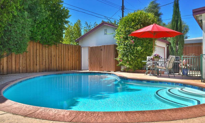 Small kidney shaped swimming pool in fenced backyard