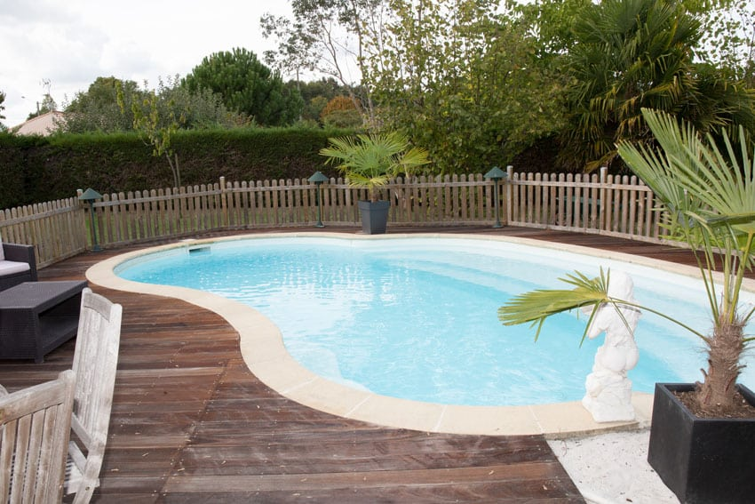 Swimming pool with wood deck and picket fence