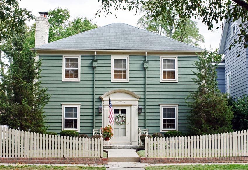 Teal house with white door and white picket fence