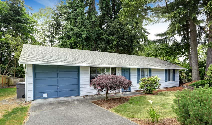 White house with blue front door garage door and window trim