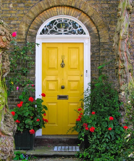 Yellow front door at rustic stone house with flowers