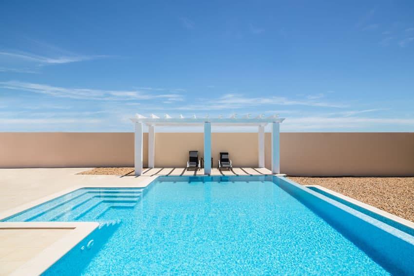 Beautiful modern blue pool with white pergola concrete patio and gravel border