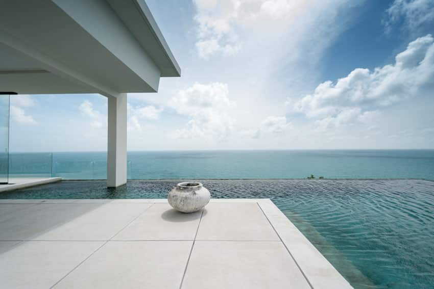 L shaped modern swimming pool with infinity edge and ocean views