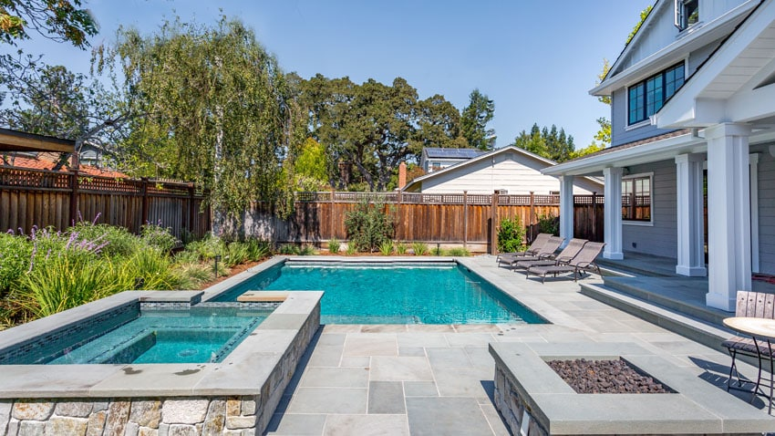 Modern in ground swimming pool with elevated hot tub and gas fire pit