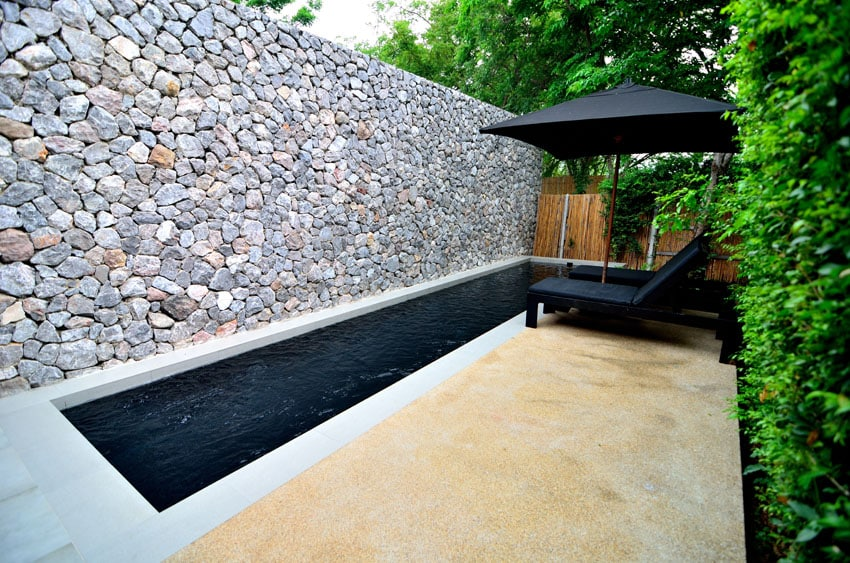 Modern rectangular pool and private villa with rock privacy wall