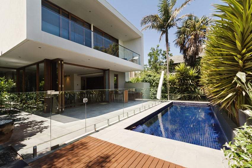 Modern swimming pool with dark blue tile and glass fence