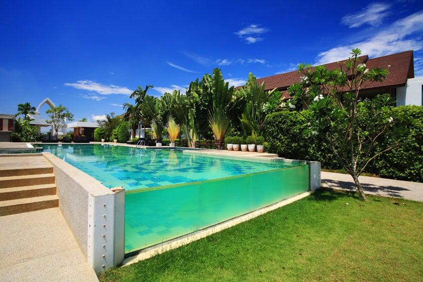 Modern swimming pool with glass infinity edge