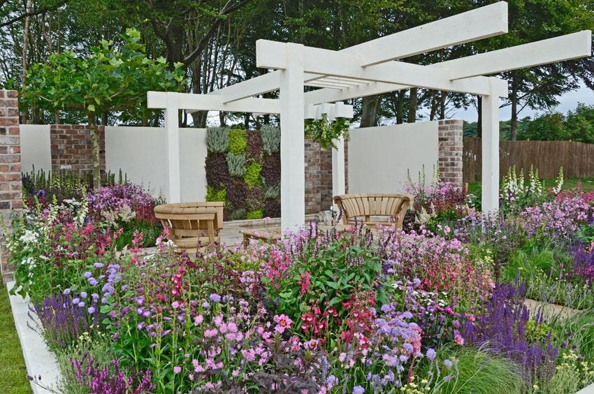 Modern white pergola in flower garden