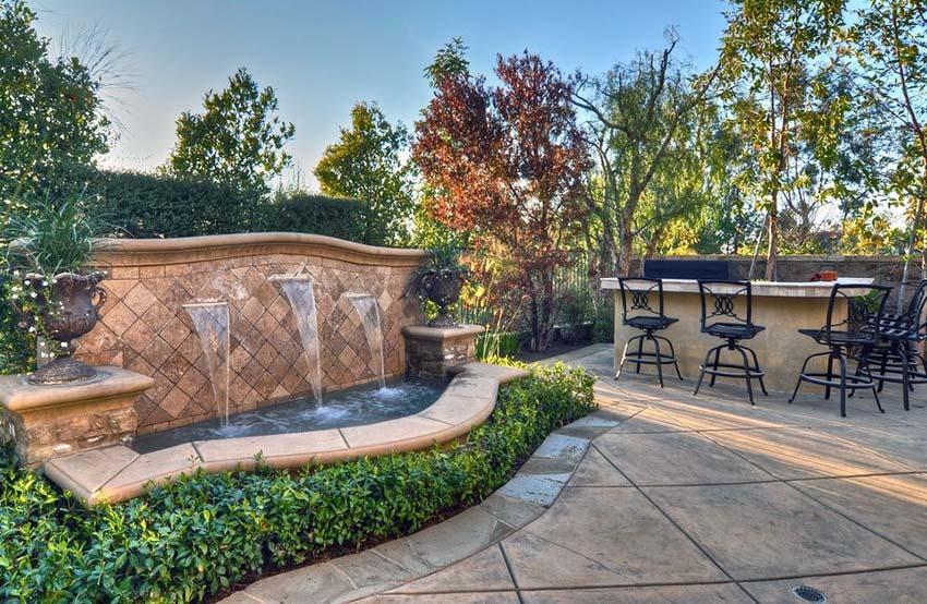 Rustic Mediterranean style water fountain in luxury backyard patio