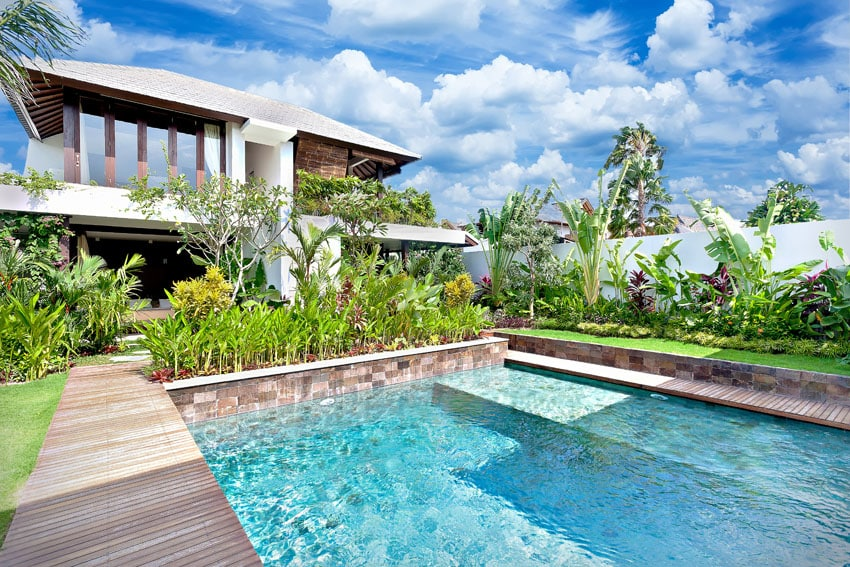 Swimming pool with sitting platform and tropical landscaping
