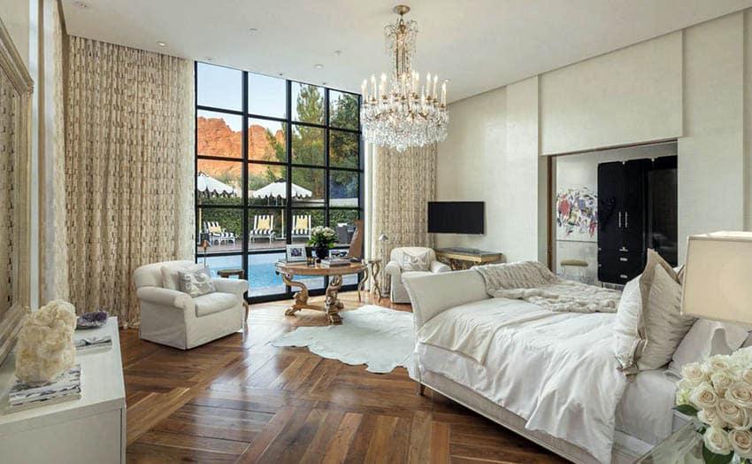 beautiful-master-bedroom-with-teak-wood-flooring-sleigh-bed-and-chandelier