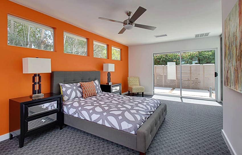 contemporary-master-bedroom-with-orange-wall-gray-carpet-and-gray-platform-bed
