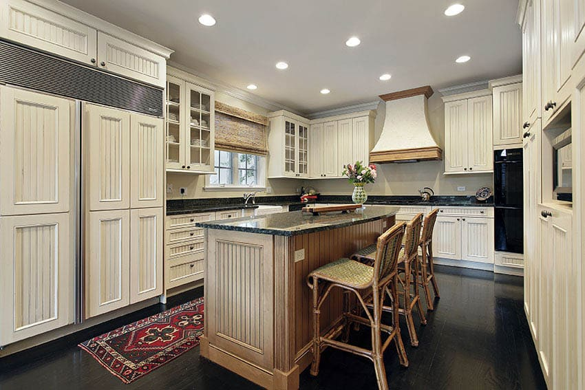 Country style kitchen with beadboard panel cabinets glass doors and beadboard island