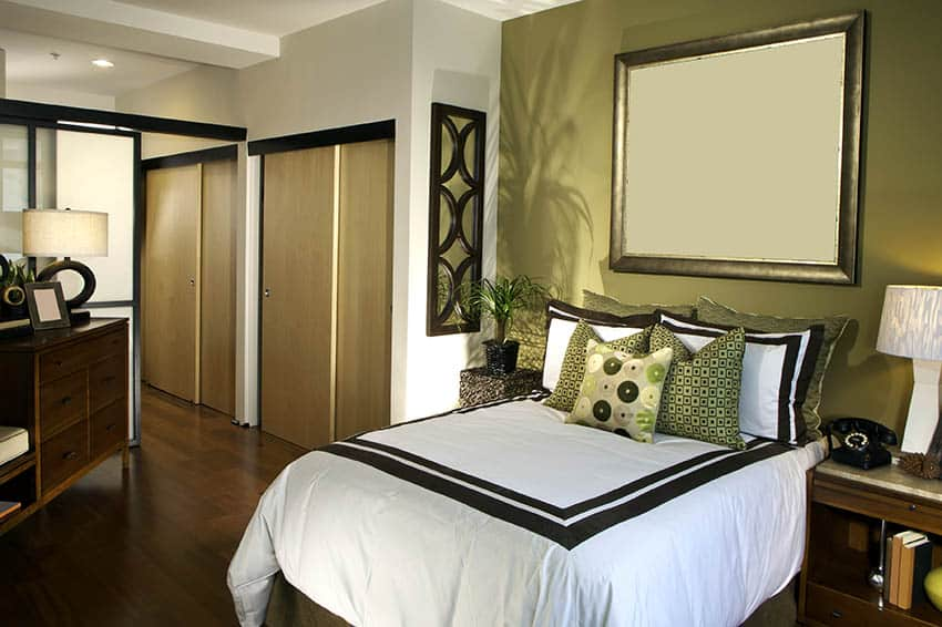 Guest bedroom with olive green accent wall