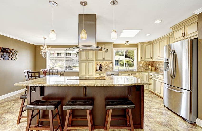 Kitchen with cream glazed kitchen cabinets and contrasting dark wood island