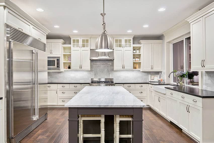 Kitchen with white shaker cabinets dark island and marble countertops