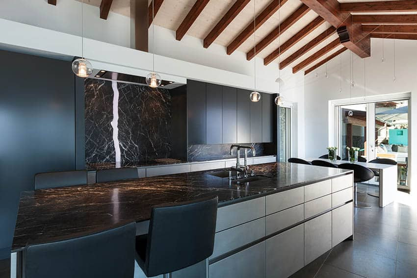 Modern kitchen with black and white cabinets and black marble countertop island