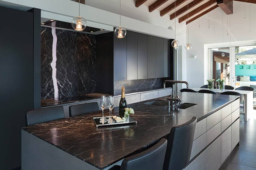Modern kitchen with black cabinets white island and black marble counter