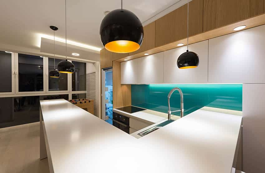Modern kitchen with green glass backsplash and white countertops