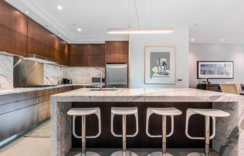 Modern kitchen with large island with carrara marble waterfall countertops