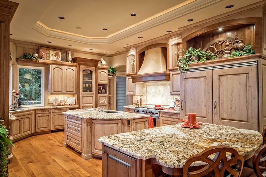 Rustic kitchen with knotty wood cabinets, custom oven hood beige granite and two islands