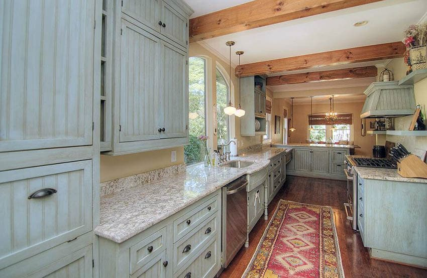Rustic kitchen with light green weathered cabinets wood floors and exposed beams