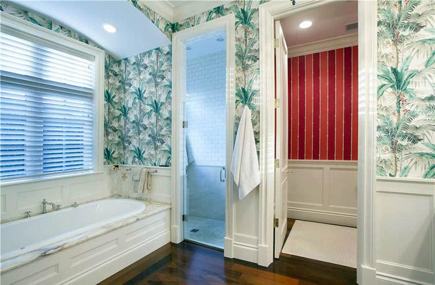 Traditional bathroom with tropical wallpaper white wainscoting and carrara marble bathtub