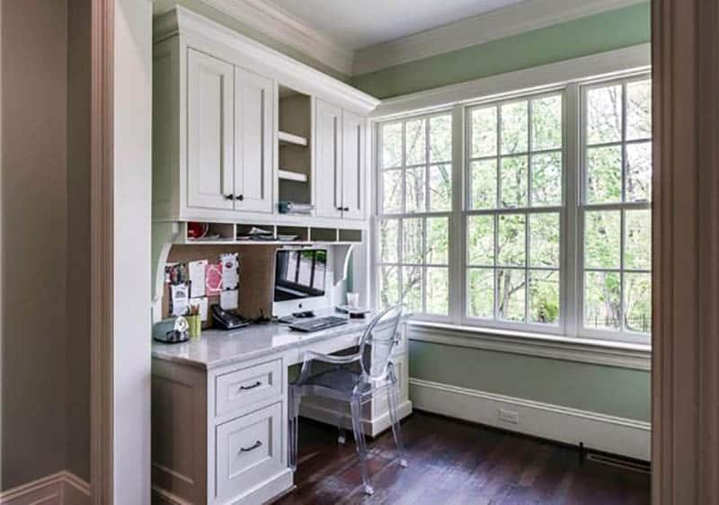 Traditional home office with light green paint and built in desk