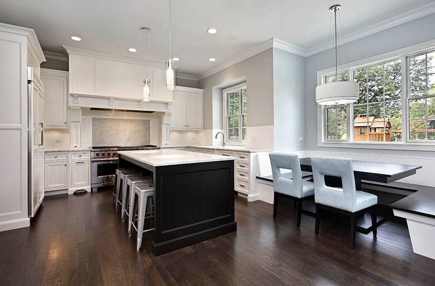 Traditional kitchen with white shaker cabinets and dark wood island with white marble counters
